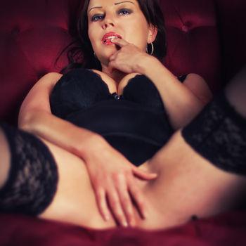 Anja liegt mit dem Rücken auf dem Sofa und spreizt die Beine während sie ihre nackte Vagina mit der rechten Hand bedeckt