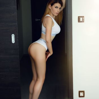 Alesia steht seitlich in weißer Wäsche und zeigt dir ihren prallen Arsch.