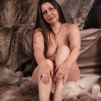 Die reife Moni nackt am Boden sitzend, zeigt ihre schönen Füße
