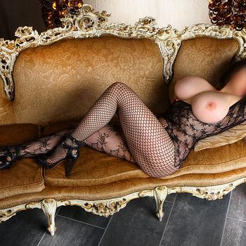 Dianarekelt sich im schwarzen Netzbody auf einer Couch und zeigt ihren sehr großen Busen