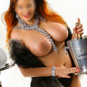 Nicole barbusig, lachend mit Champagnerflasche
