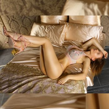 Kira rekelt sich in zarten pastellfarbenen Dessous auf einem Bett