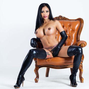 Rerei mnackt mit schwarzen Wetlokk Handschuhen und Strümpfen auf einem Sessel mit der Hand zwischen den gespreizten Beinen