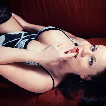Anja auf dem Rücken liegend, mit verführerischem Blick und leichtem Biss auf ihren Zeigefinder