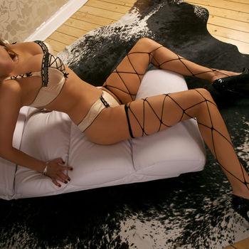 Anika sitzt mit gespreizten Beinen in zarter Wäsche