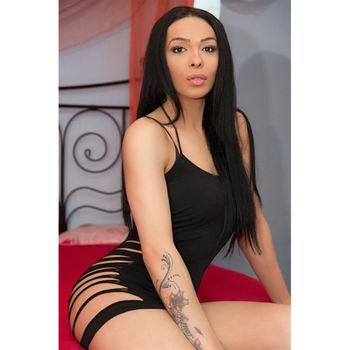 TS Angelina in schwarzem Kleid auf einem Bett sitzend.