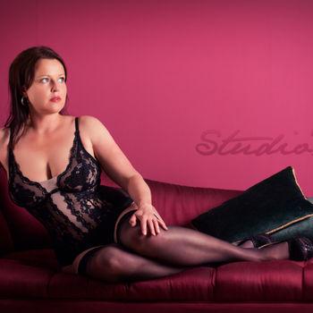 Anja in schwarzen Dessous auf dem Sofa liegend mit devotem Blick
