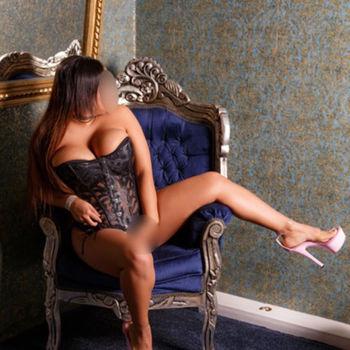 Latina Ruby trägt eine sexy Korsage und fasst sich provokativ zwischen die Beine.