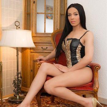 die schöne TS Angelina in schwarzem Top seitlich sitzend, zeigt ihre schönen, langen Beine.