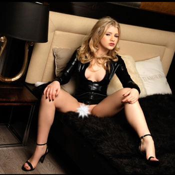 Sophie Teen Mit gespreizten Beinen in enger Lederjacke auf einem Bett sitzend