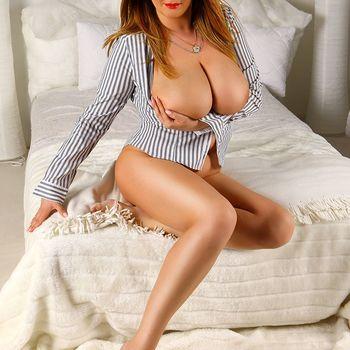 Die brünette Laura umfasst sinnlich ihre großen Brüste mit dem linken Arm.