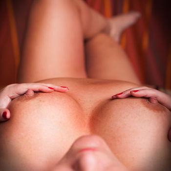 Sandy liegt, berührt ihre Brüste und zeigt ihre harten Brustwarzen