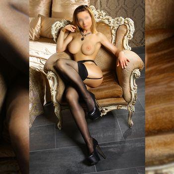 Kira sitzt mit nacktem Busen und schwarzen Strapsen in einem Sessel und zeigt ihre langen Beine