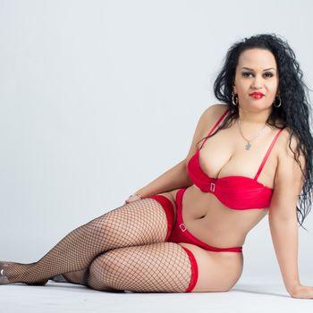 Natalia in schwarzen Netzstrümpfen und roten Dessous auf dem Boden sitzend