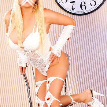 Anja im sexy weißem Body und mit raffinierten Strümpfen, kniend auf einem Stuhl