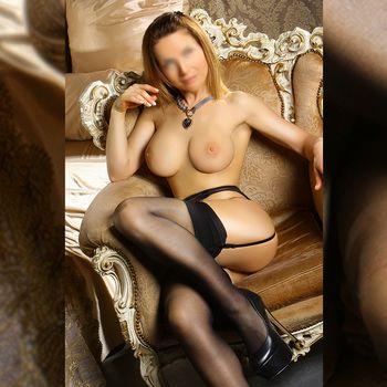 Kira sitzt mit nacktem Busen und schwarzen Strapsen in einem Sessel und zeigt ihre langen Beine in Nahaufnahme