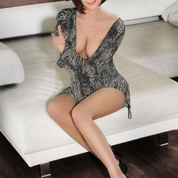 Alexa zeigt ihre langen Beine sitzend in einem verspielten Kleid.