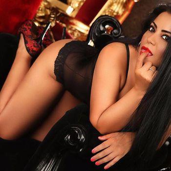 Sexy Latina Angela kniend in schwarzen Dessous, leckt an ihrem Finger