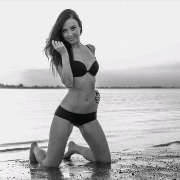 Mila kniet am Strand in sexy Bikini.
