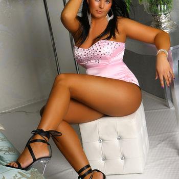 Schwarzhaarige Natalie sitzend in rosa Korsage