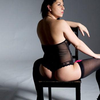 Laura rücklings auf einem Stuhl, schaut sexy über ihre rechte Schulter.