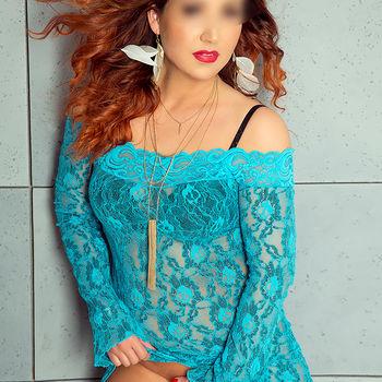 die schöne Maja mit Wind im Haar in einem türkisen Spitzenkleid das sie hochzieht aber ihre Vagina mit der anderen Hand bedeckt