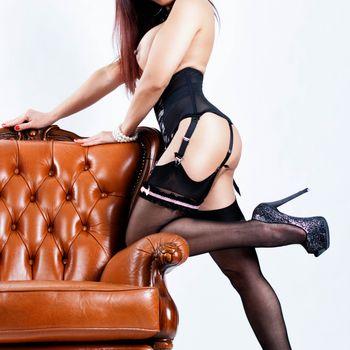 Nadja im Tailenmieder, Strümpfen und High Heels, lehnt kniend an einem Sessel