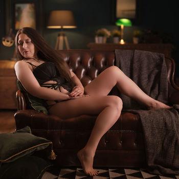 Moni sitzt in schwarzer Wäsche angelehnt auf einem Sofa, ihre schönen Beine streckend.