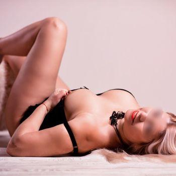 Dyana auf dem Rücken liegend mit laszivem Lächeln, legt eine Brust frei und zeigt ihren Nippel