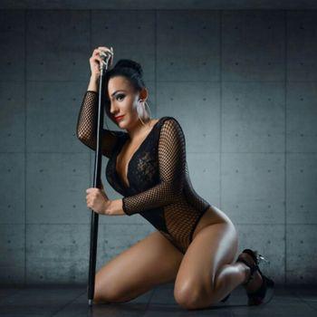 Mia in erotisch, kniender Pose an einer Polestange