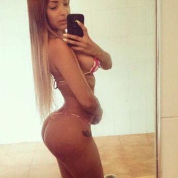 Blondine Alina zeigt dir seitlich stehend ihre sexy Kurven.