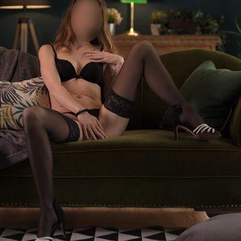 Michelle sitzt mit gespreizten Beinen auf dem Sofa und fasst sich zwischen die Beine