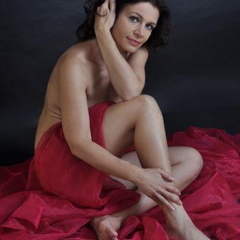 Reife Marta sitzt nackt am Boden nur ganz leicht von rotem Stoff bedeckt
