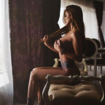 Die schlanke Britney sitzt nackt seitlich auf einem Sofa, bedeckt mit einer Hand ihre Brust und spielt mit der anderen mit ihren langen Haaren.