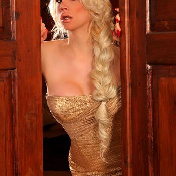 TS Kristina Prado mit langem Zopf und goldenem Kleid in der geöffneten Tür stehend