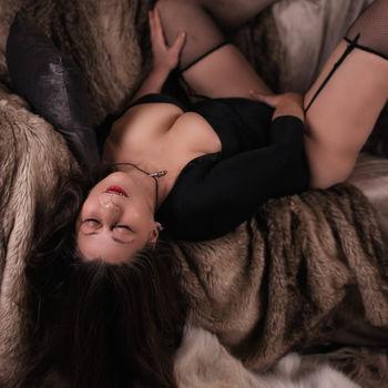 Moni in schwarzer Wäsche auf dem Sofa liegend, verwöhnt sie sich selbst