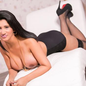 Die schöne Manuella auf dem Bauch liegend und auf die Ellenbogen gestützt, zeigt sie ihre schönen, wohlgeformten Brüste