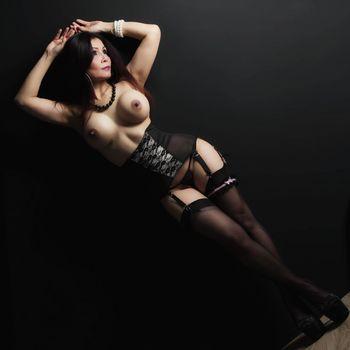 Nadja steht in Reizwäsche mit nackten Brüsten in licht und Schatten