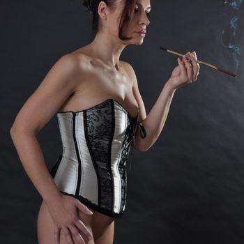 Schöne Marta nur in silberner Korsage, eine Zigarettenspitze rauchend