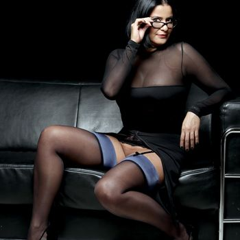 Esmeralda sitzend mit dezent gespreizten Beinen, zeigt ihren Venushügel wobei die Strapse und schwarze Strümpfe trägt