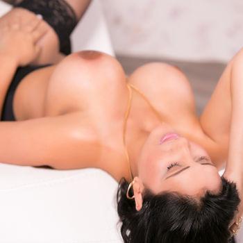 Manuella entspannt auf dem Rücken liegend, kommt ihre samtweiche Haut zur Geltung