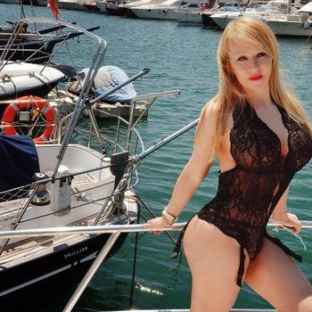 Gina lehnt in schwarzer Spitzenwäsche an einem Bootsgeländer.