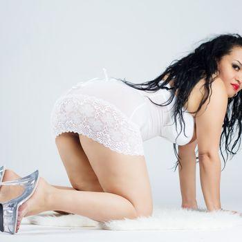 Natalia kniet auf allen Vieren und trägt transparente High Heel und ein weißes, enges Minikleid