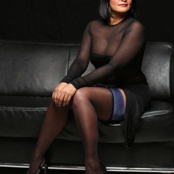 die sinnliche Esmeralda im schwarzen Kleid und Strümpfen auf einer Ledercouch sitzend, mit schweifendem Blich durch ihre Brille