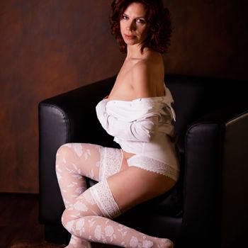 Marta mit weisser Wäsche und offenem Hemd im Lounge Sessel