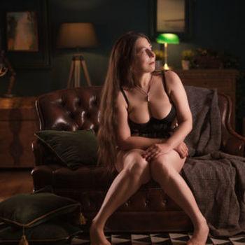 Moni sitzend, ihr üppiges Dekolleté in schwarzem Body zeigend.