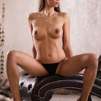 Lenka sitzt mit gespreizten Beinen nur im schwarzen Slip