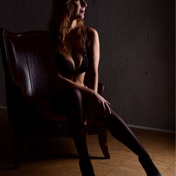 Die langhaarige Nadine sitzt in schwarzen Strümpfen nach vorne gelehnt auf einem Stuhl, man sieht ihre schlanke Silhouette.