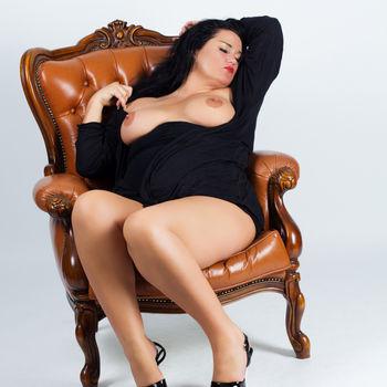 Sandy liegt im schwarzen Kleid und nacktem Busen in einem Chesterfield Sessel