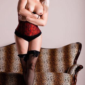 Dyana steht in schwarzen Netzstrümpfen und roter Unterbrustkorsage und zeigt ihre süßen Brüste